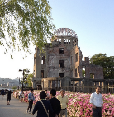 The skeleton of a building that structurally survived the atomic bomb. It is a sunny day, there are bushes with pink flowers in front of it, a weeping willow in the top L corner. People are walking by on the sidewalk in front of the building.