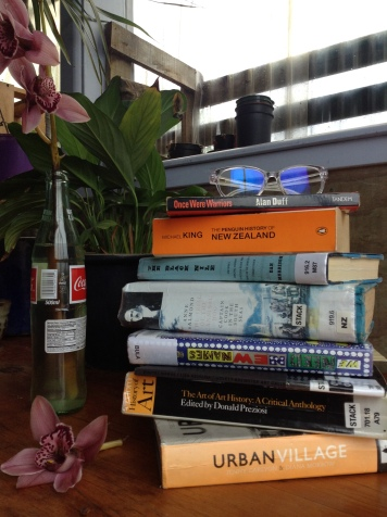 Stack of books with glasses sitting atop. Pink Orchid on the wood table. Green plant in background.