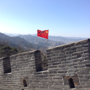 The Chines flag waves in the wind above the Great Wall. There are mountains in the distance, and a blue sky.