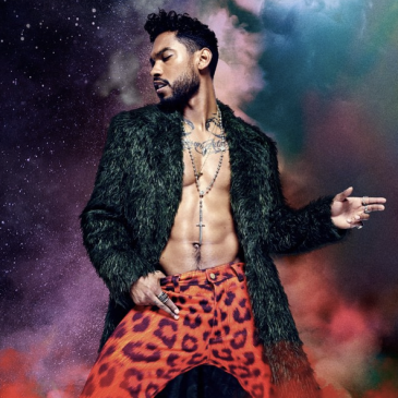 Singer Miguel stands with his legs apart, wearing red leopard print pants and a green fur coat with no shirt underneath. He wears a rosary and his head is turned right with eyes closed. The background looks like outer space infused with red, blue and white clouds.