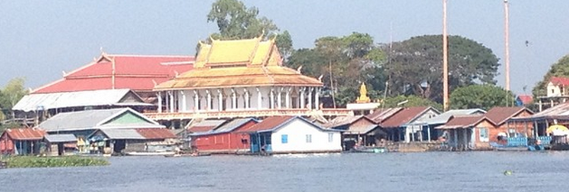 A white temple with a golden roof, a group of houses with tin roofs and wooden walls that are floating on the river near the banks.