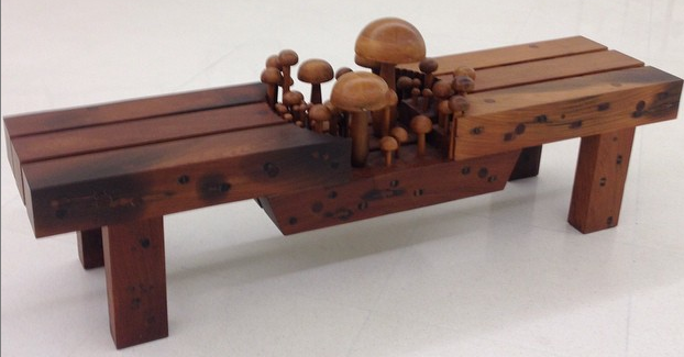 Chestnut brown wooden bench has carved mushrooms sprouting from the middle.