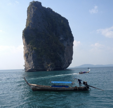 A giant rock with trees growing on it thrusts up out of the blue green ocean. There are two wooden speed boats in front. The sun is shining.