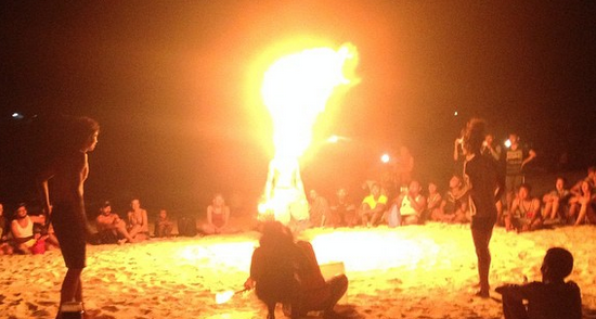 A group of people sit around a ring of 3 men breathing fire. It is night.