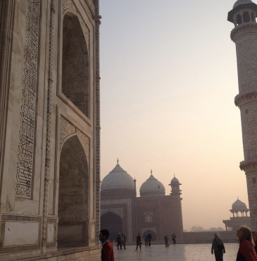 Sunrise makes the sky pink, white, light blue. There are red and white brick buildings (the Taj Mahal and a Taj Mahal gate house) with Arabic written on the sides, and a white tower in the right corner. There are people walking on the verandah, some looking up at the Taj Mahal.