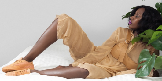 Dark brown skinned woman with chin length black hair, worn down, reclines in a camel colored outfit with creamsicle orange sneakers.
