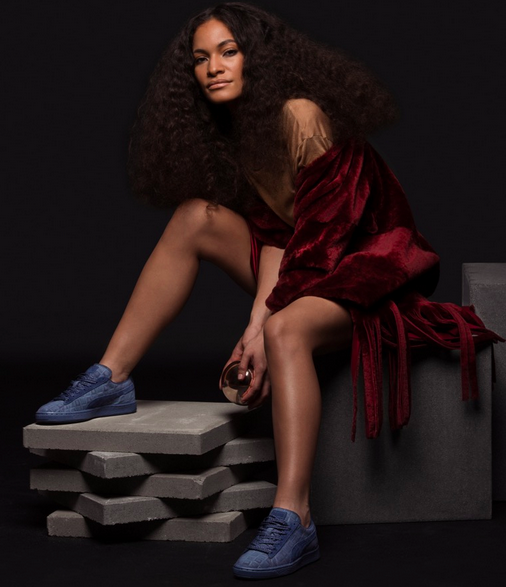 Light brown skinned woman draped in a crimson shawl with dark blue puma sneakers sits and looks at the camera. Her hair is long and curly, and worn down.