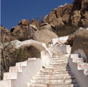 Dirty white stairs set in a mountainside; big brown boulders are on either side The sky is deep, bright blue.