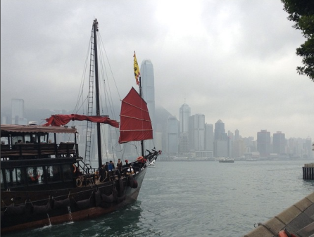 Traditional Chinese Junk sails in the Hong Kong Harbor with tourists aboard. It is a cloudy day. There is a city skyline behind the ship.