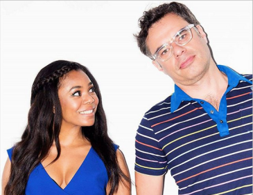 Regina Hall and Jemaine Clement are against a stark white backdrop. Hall wewars a blue sleeveless dress and smiles and looks up and to the left at Jemaine. Jemaine is wearing glasses and a multicolor striped collared tee.